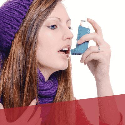 Frau sprüht Asthmaspray