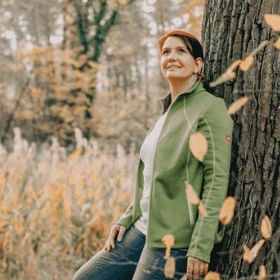 Claudia Beilicke am Baum lehnend und nach oben schauend