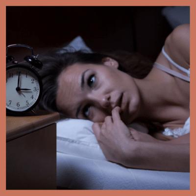 Frau liegt im Bett und starrt auf den Wecker